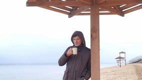 Giovane romantico che si rilassa sulla spiaggia con, sul tè o sul caffè caldo bevente dal termos Sera calma e accogliente Fotografie Stock