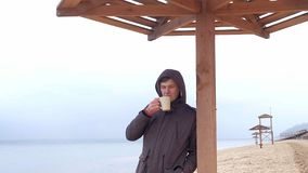 Giovane romantico che si rilassa sulla spiaggia con, sul tè o sul caffè caldo bevente dal termos Sera calma e accogliente Fotografia Stock Libera da Diritti