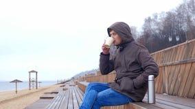 Giovane romantico che si rilassa sulla spiaggia con, sul tè o sul caffè caldo bevente dal termos Sera calma e accogliente Immagine Stock