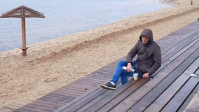 Giovane romantico che si rilassa sulla spiaggia con, sul tè o sul caffè caldo bevente dal termos Sera calma e accogliente Fotografia Stock