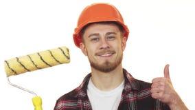 Giovane rullo di pittura maschio felice della tenuta del costruttore che mostra i pollici su fotografie stock libere da diritti