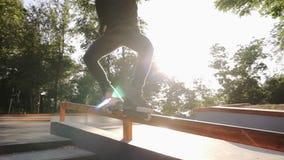 Giovane rullo negli scorrevoli neri dell'abbigliamento casual tramite un tubo in uno skatepark Un giovane atleta esegue un trucco archivi video