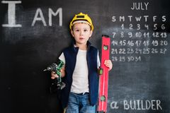 Giovane ` s del ragazzo che sta con il cacciavite vicino alla lavagna Giovane costruttore Concetto di progetto creativo per il ca immagine stock