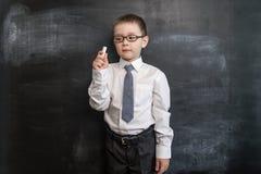 Giovane ` s del ragazzo che tiene un gesso vicino alla lavagna Di nuovo al concetto del banco Ragazzo prescolare astuto ed abile Immagine Stock