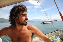 Giovane Sailaing maschio selvaggio attraverso le isole di Paraty Rio fa Janeiro Immagine Stock