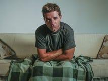 Giovane salone triste e disperato dell'uomo a casa che si siede allo strato del sofà che sembra sensibilità di sofferenza emozion Fotografie Stock Libere da Diritti