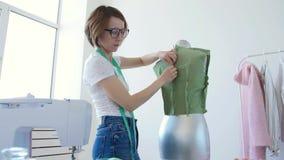 Giovane sarto femminile grazioso che lavora con il tessuto del panno in officina archivi video