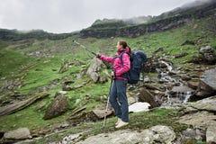 Giovane scalatore femminile che sta paesaggio pieno d'ammirazione del bordo della roccia sul bello delle montagne rocciose e dei  immagine stock