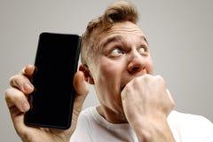 Giovane schermo bello dello smartphone di rappresentazione dell'uomo isolato su fondo grigio nella scossa con un fronte di sorpre fotografie stock