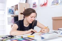 Giovane schizzo femminile del disegno dell'artista facendo uso dello sketchbook con la matita nel suo luogo di lavoro in studio R Immagini Stock Libere da Diritti