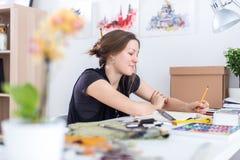 Giovane schizzo femminile del disegno dell'artista facendo uso dello sketchbook con la matita nel suo luogo di lavoro in studio R Immagine Stock