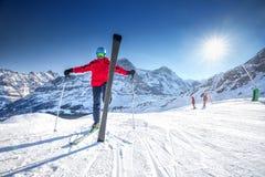 Giovane sciatore caucasico attraente con lo sci sul pendio dello sci Fotografia Stock Libera da Diritti
