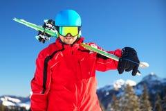 Giovane sciatore caucasico attraente con lo sci sul pendio dello sci contro la m. Fotografie Stock