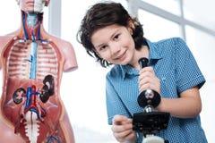 Giovane scienziato ammirevole che installa un microscopio Immagine Stock