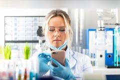 Giovane scienziato attraente della donna che utilizza smartphone nel laborat Fotografia Stock