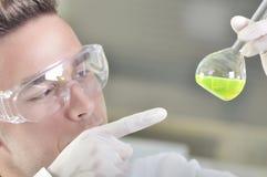 Giovane scienziato attraente dello studente di PhD osservando lo spostamento di colore dopo il destillation della soluzione in la Fotografia Stock