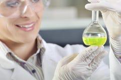 Giovane scienziato attraente dello studente di PhD osservando lo spostamento di colore dopo il destillation della soluzione in la Fotografie Stock Libere da Diritti