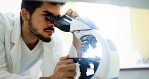Giovane scienziato che guarda tramite il microscopio in laboratorio Fotografia Stock