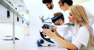 Giovane scienziato che guarda tramite il microscopio in laboratorio immagine stock
