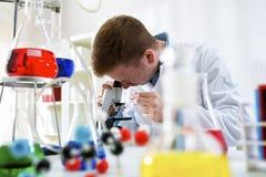 Giovane scienziato che lavora con il microscopio al laboratorio della clinica Fotografia Stock