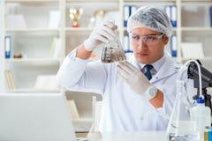 Giovane scienziato del ricercatore che fa un expe di contaminazione della prova di acqua Fotografie Stock