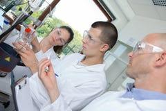 Giovane scienziato dello studente di phd che guarda tramite il microscopio Fotografia Stock Libera da Diritti