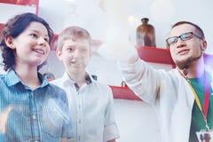 Giovane scienziato divertente che mostra gli allievi di reazione chimica Fotografia Stock Libera da Diritti