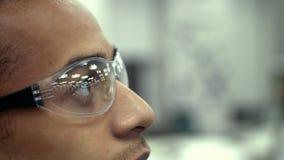 Giovane scienziato maschio che esamina una provetta riempita di sangue che lavora al laboratorio stock footage