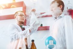 Giovane scienziato maschio che mostra ad allievo adolescente esperimento chimico nel laboratorio Immagine Stock