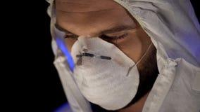 Giovane scienziato in primo piano della maschera protettiva, esperimento pericoloso, epidemia fotografia stock