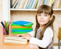 Giovane scolara che legge un libro esaminando macchina fotografica Immagine Stock