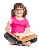 Giovane scolara con il libro che mostra i pollici su Isolato su bianco Immagini Stock Libere da Diritti