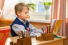 Giovane scolaro che si siede dietro uno scrittorio del banco Fotografia Stock