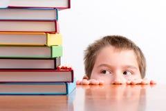 Giovane scolaro premuroso che osserva sui suoi libri Fotografia Stock Libera da Diritti