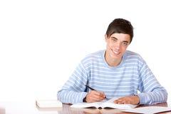 Giovane scrittorio bello felice del learningon dell'allievo maschio Fotografia Stock