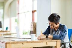 Giovane scrittura asiatica seria dell'uomo in taccuino e computer portatile usando Fotografie Stock Libere da Diritti