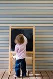 Giovane scrittura caucasica sveglia del ragazzo su una lavagna Immagine Stock Libera da Diritti