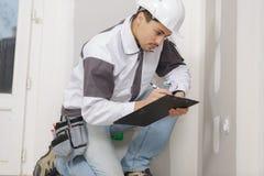 Giovane scrittura del costruttore qualcosa in elmetto protettivo con la lavagna per appunti fotografia stock