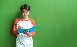Giovane scrittura del ragazzo dell'adolescente sul taccuino blu che pende a wal verde Fotografia Stock Libera da Diritti