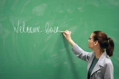 Giovane scrittura dell'insegnante sulla scheda Fotografia Stock