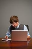 Giovane scrittura dell'uomo di affari sul blocchetto per appunti Fotografia Stock