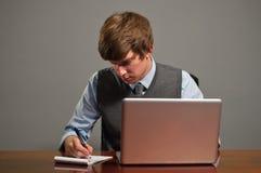 Giovane scrittura dell'uomo di affari sul blocchetto per appunti Fotografie Stock Libere da Diritti