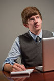Giovane scrittura dell'uomo di affari sul blocchetto per appunti con il computer portatile Fotografia Stock Libera da Diritti