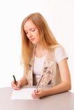 Giovane scrittura della donna dell'allievo in taccuino Fotografie Stock Libere da Diritti