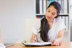 Giovane scrittura della donna di affari in diario Immagine Stock Libera da Diritti