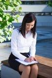 Giovane scrittura della donna di affari qualcosa sulla lavagna per appunti nel parco della città Fotografia Stock Libera da Diritti
