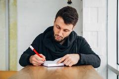 Giovane scrittura maschio dell'uomo d'affari su un blocco note sullo scrittorio di legno nel negozio del caffè del caffè Fotografia Stock Libera da Diritti