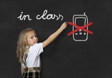 Giovane scrittura minore dolce della scolara con il gesso circa non facendo uso del telefono cellulare nella classe di scuola Fotografia Stock Libera da Diritti