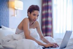 Giovane sedile della donna di colore a letto Fotografia Stock