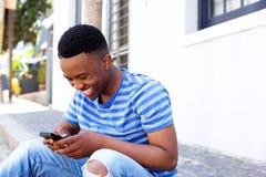 Giovane seduta africana dell'uomo esterna ed esaminare cellulare Immagine Stock